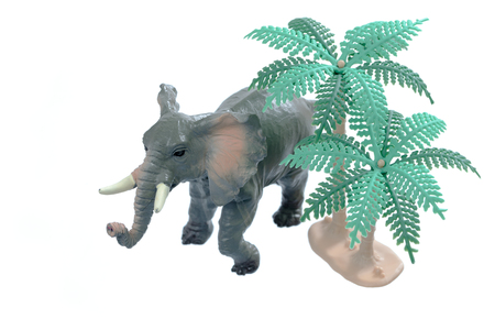 toy elephant: A small toy elephant with trees isolated on a white background.