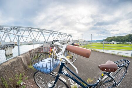 fisheye: A close up fisheye shot of a bicycle with a bridge in the background.