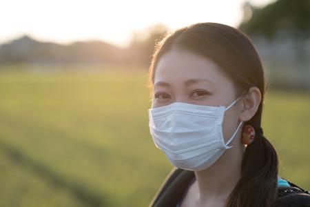 야외에서 그녀의 뒤에 밝은 일몰 시골에서 외과 마스크를 착용하는 젊은 일본 여자.