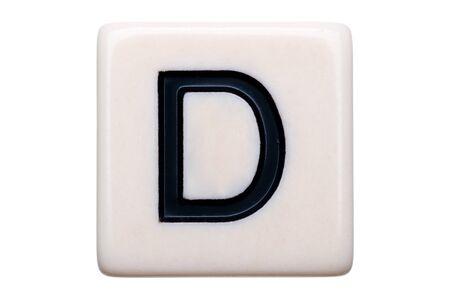 Een macroschot van een speltegel met de brief D op het op een witte achtergrond.