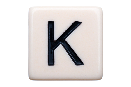 letter k: A macro shot of a game tile with the letter K on it on a white background.