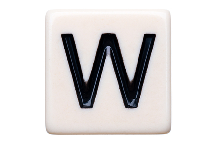 letter w: A macro shot of a game tile with the letter W on it on a white background. Stock Photo