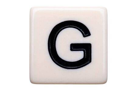 g alphabet: A macro shot of a game tile with the letter G on it on a white background.