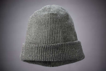 A studio shot of a grey knit cap suspended on a grey background lit with a natural vignette.