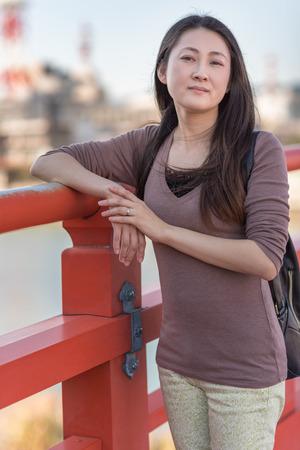 A young Japanese girl posing on an orange bridge in Japan.