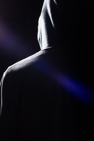 hooded sweatshirt: A dark silhouette of a man wearing a hooded sweatshirt with very dramatic shadows, lens flare and dust in the air. Stock Photo