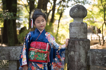 religious clothing: A young Japanese girl in a kimono outdoors on a stone bridge at a shrine. Stock Photo