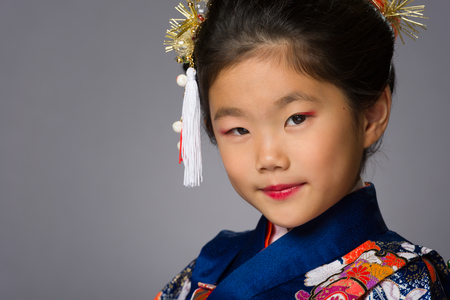 A cute young Japanese girl wearing a Kimono on a grey background.