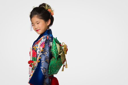 A cute young Japanese girl wearing a Kimono on a white background. Banco de Imagens