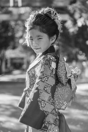 religious clothing: A young Japanese girl in a kimono outdoors at a shrine. Stock Photo