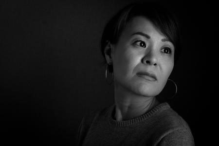 mujer pensativa: Un tiro en la cabeza en blanco y negro de una mujer que busca japonesa de mediana edad triste.