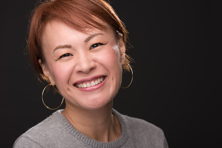 A headshot of a smiling middle aged Japanese woman. 版權商用圖片