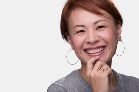 approachable: A headshot of a smiling middle aged Japanese woman on a white background.