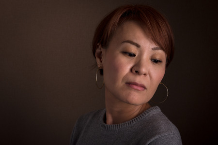 sad person: A headshot of a sad looking middle aged Japanese woman.