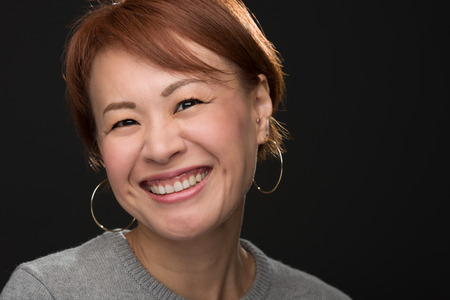 short cut: A headshot of a smiling middle aged Japanese woman. Stock Photo