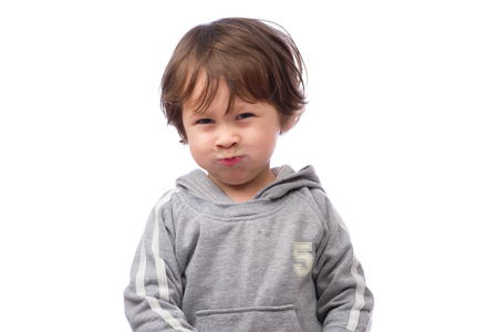 3 year old: A cute 3 year old boy with an angry expression on a white background. Stock Photo