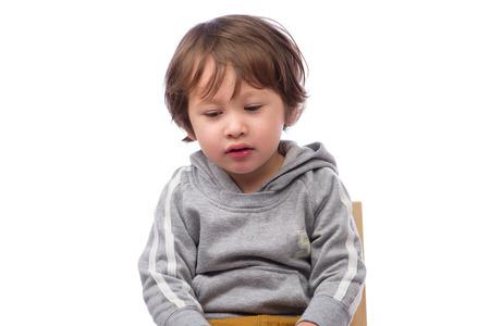 白い背景に悲しそうな表情でかわいい 3 歳の男の子。