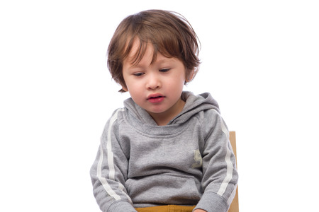 3 year old: A cute 3 year old boy with a sad expression on a white background.
