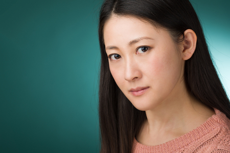 early 30s: A headshot of a Japanese woman in hear early 30s on a simple green background.