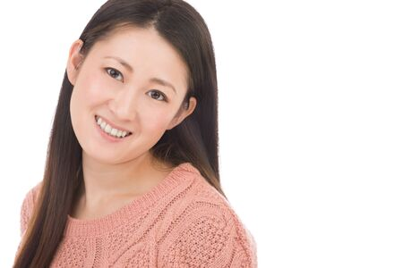 A headshot of a Japanese woman in hear early 30s on a simple white background. Stock Photo