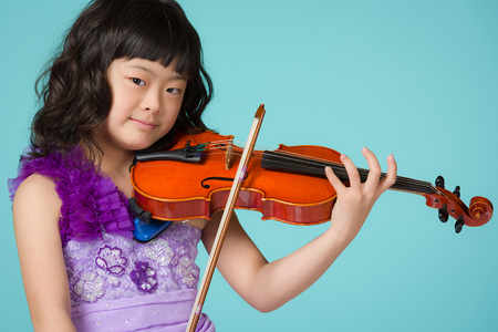 A portrait of a cute, happy and young Japanese girl in a purple dress on a blue background with a violin.