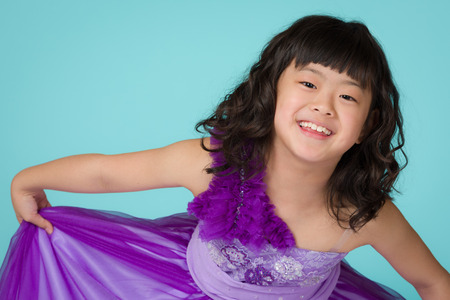 bowing head: A portrait of a cute, happy and young Japanese girl in a purple dress on a blue background.