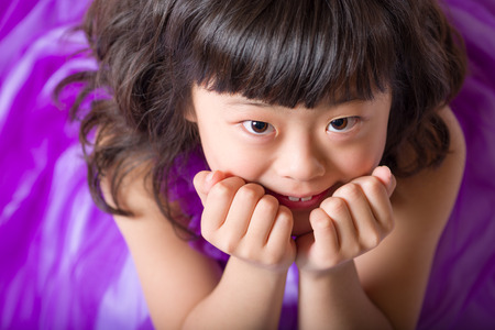 A portrait of a cute, happy and young Japanese girl in a purple dress. 版權商用圖片