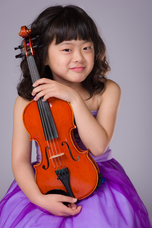 A portrait of a cute, happy and young Japanese girl in a purple dress on a grey background with a violin.
