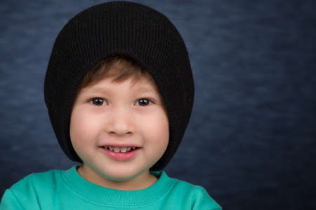 A smiling young boy wearing a knit winter hat.