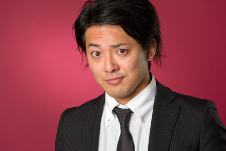 collared shirt: A headshot style portrait of a young Japanese man wearing a business suit on a red background with a slight smile.