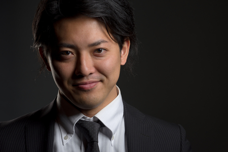 hint: A low key portrait of a young Japanese man in a business suit with a hint of a smile on his face. Stock Photo