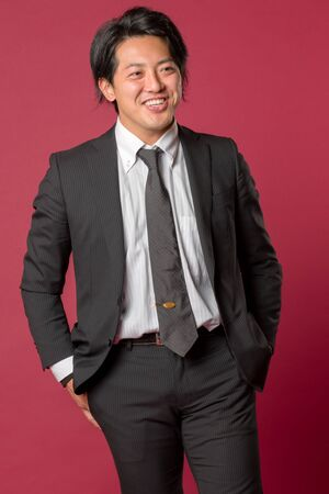 collared shirt: A half body portrait of a young Japanese man in a business suit laughing on a red background.