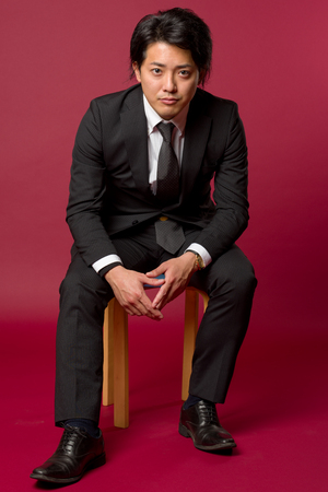 collared shirt: A portrait of a young Japanese man in a business suit sitting on a stool in a cool pose. Stock Photo