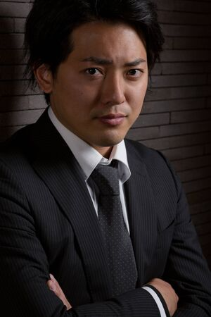 A low key portrait of a young Japanese man in a business suit with a serious expression on his face. Stock Photo
