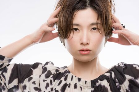 A high key headshot of a young and beautiful Japanese woman in a strong and confident pose on a white background.