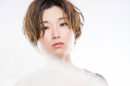 cutting through: A high key headshot of a young and beautiful Japanese woman with a blurred lace sheet fluttering in front and cutting through the picture for artistic effect shot on a white background.