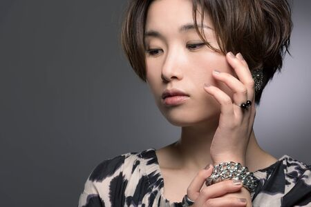 A portrait of a young, beautiful and very fashionable Japanese woman posed gently on a dark background. 版權商用圖片