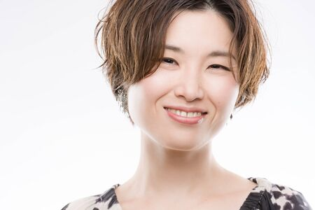 high key: A high key headshot of a smiling, beautiful and young Japanese woman on a white background. Stock Photo