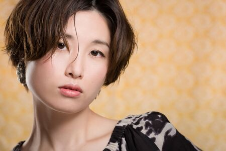 A portrait of a  young and beautiful Japanese woman shot on a yellow and white lace background.