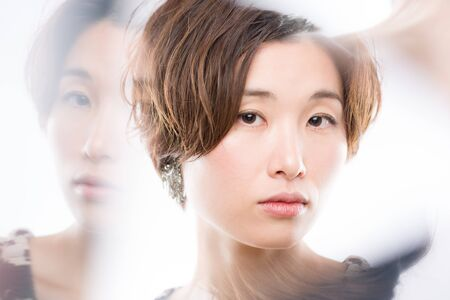 A high key headshot of a young and beautiful Japanese woman shot through mirrors arranged to get reflections around her face for artistic effect shot on a white background.