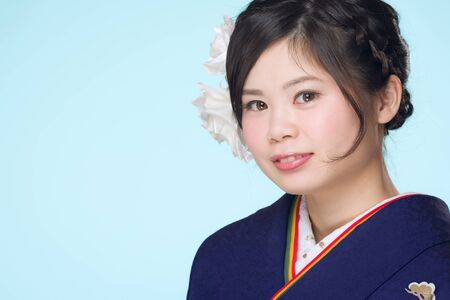 A portrait of a beautiful young Japanese girl in a blue kimono for her coming of age ceremony on her 20th birthday.