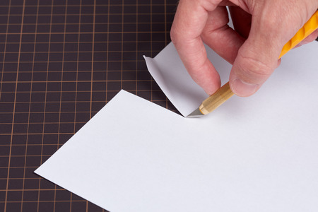 A hand holding a utility knife with a yellow handle cutting a piece of white paper on a cutting mat.