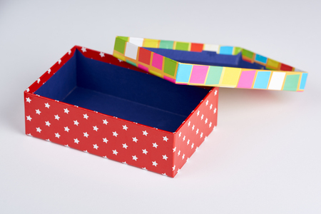 A colorful box and lid with a polka dots and squares design on white.