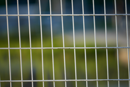 A white wire fence slightly leaning to the left with a very blurred background.