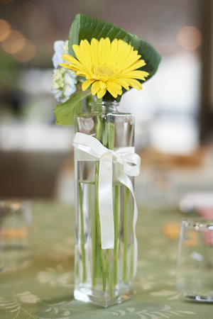 A small glass vase of yellow flowers on a green table at a wedding reception. 版權商用圖片