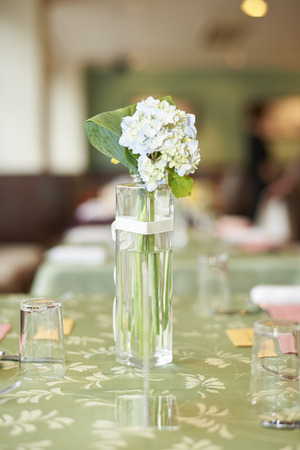 A small glass vase of white flowers on a green table at a wedding reception.