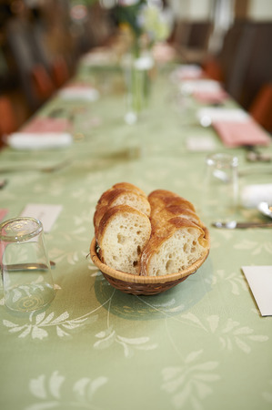A small bowl of a cut baguette on a green table at a wedding reception.