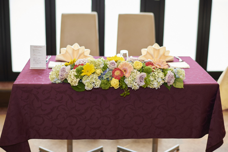 A large bouquet of assorted flowers on the head table at a wedding reception with a red table cloth and large windows behind it. 版權商用圖片