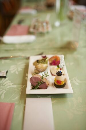 A small plate of appetizers on a green table at a wedding reception with a blank name card in front.