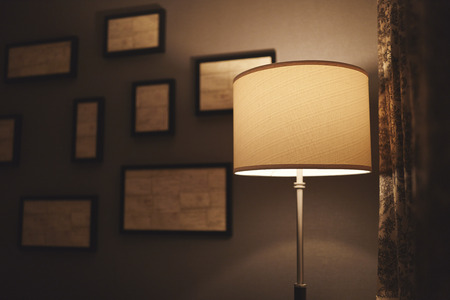 A lamp in a dark corner of a hotel room with abstract frames out of focus on the wall behind it and a curtain to the right.
